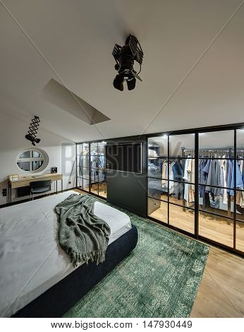 Wonderful modern bedroom with cloakroom with glowing lamps, white walls. On the floor there is green carpet. Also there is bed, table with chair, TV, round window on the wall and window at the top.