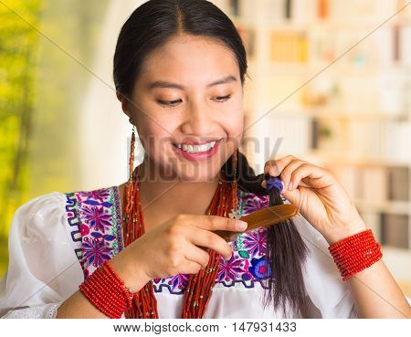 Beautiful hispanic woman wearing white blouse with colorful embroidery, using small hairbrush during makeup routine, garden background.
