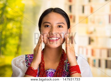Beautiful hispanic woman wearing white blouse with colorful embroidery, applying cream onto face using both hands during makeup routine, smiling happily, garden background.