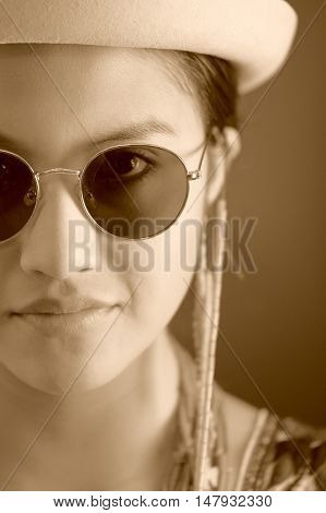Beautiful hispanic model wearing light colored blouse, trendy sunglasses with matching hat, smiling posing for camera, studio background, black and white edition.