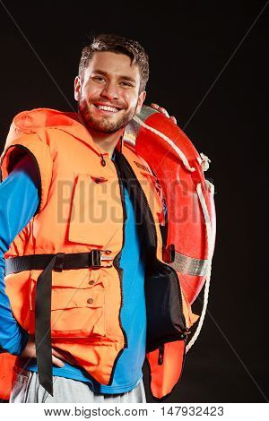 Lifeguard in life vest jacket with ring buoy lifebuoy. Man supervising swimming pool water on black. Accident prevention.
