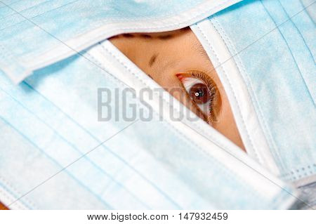 Closeup eye of woman peeking out from total facial cover, preparing for cosmetic surgery concept.