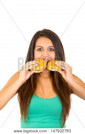 Beautiful young woman posing for camera holding two hamburgers next to mouth, smiling happily, white studio background.