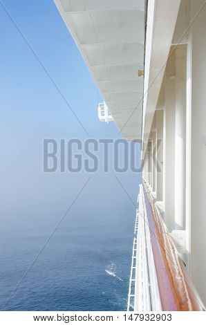 View from the balcony of a cruise ship of the fog lifting from the sea.