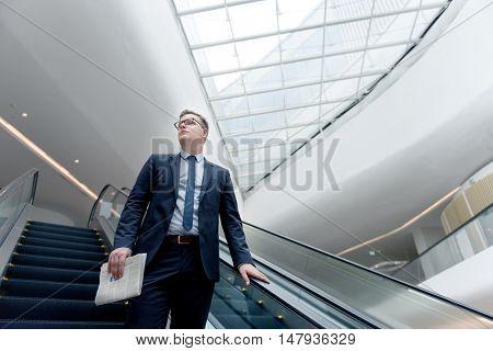 Businessman Walking Down Escalator Concept