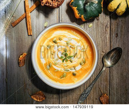 Roasted pumpkin soup with cream and pumpkin seeds on wooden background. Toning.