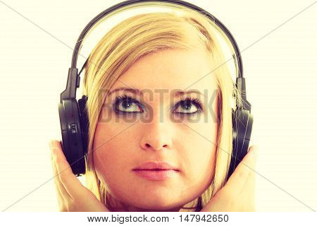 Music concept. Blonde young pretty woman in big black headphones on her head. Girl listening to music song sound.
