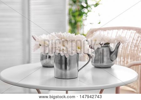 White chrysanthemum in cup on light table