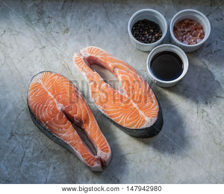 Two fresh raw salmon steaks on marble table with soy sauce and spices.