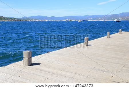 Wooden Boat Mooring Bollards On Jetty By Blue Ocean