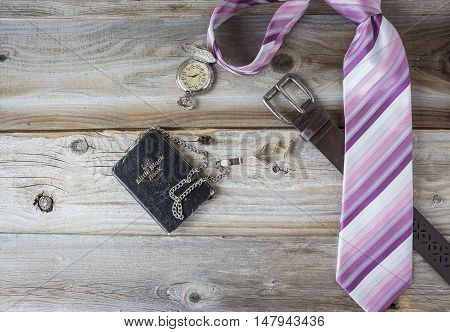 horizontal image of man's business suit accessories with a necktie and belt a pocket watch and cuff links lying on a rustic old wood surface with room for text.