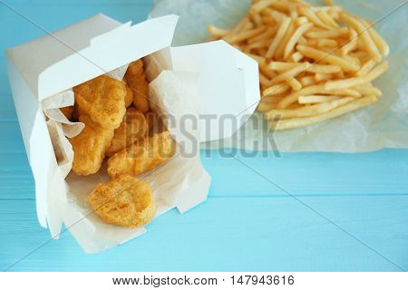 Tasty chicken nuggets in paper box and fries on table