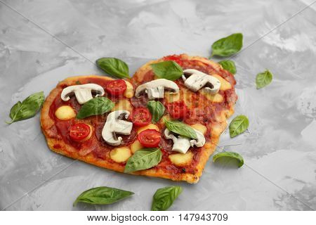 Tasty pizza in heart shape and fresh basil leaves on table