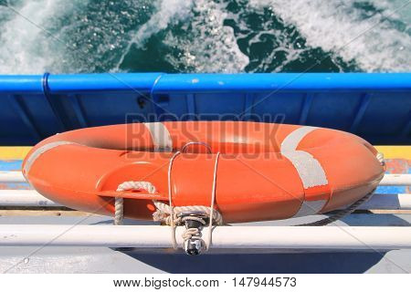 Lifebelt On Rear Of A Boat, With White Foam Of The Wake In Background