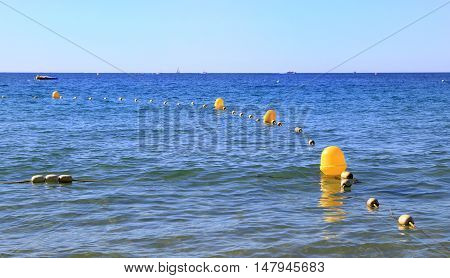 Yellow Buoys And Rope Showing Safe Swimming Zone In A Clear Blue Sea