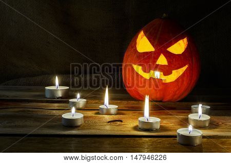 Halloween symbol smiling pumpkin lantern and burning candles. Halloween jack-o-lantern and burning candles background.