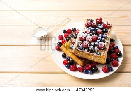 Breakfast waffles with fresh berries and powder sugar. Soft Belgian waffles with blueberry raspberry and blackcurrant.