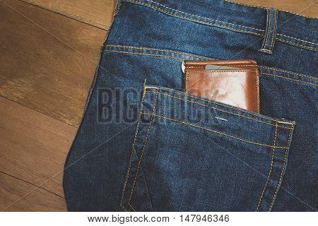brown leather wallet in jeans back pocket blue.