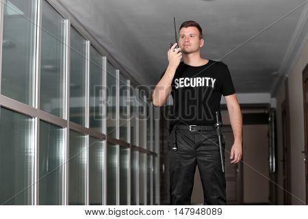 Security man in corridor using portable radio