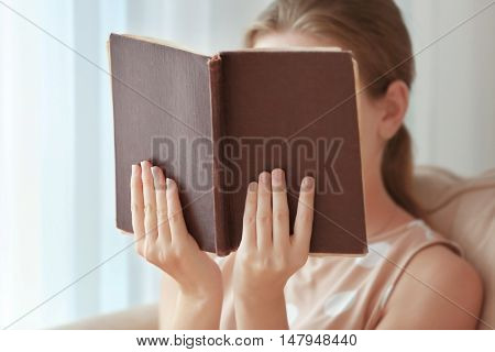 Woman reading old book at home