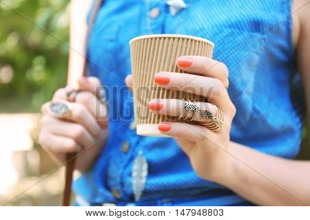 Close up of female hand with beautiful bijouteries holding cup of coffee