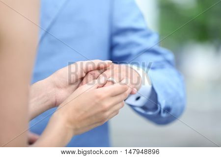 Bride putting ring on groom finger outdoor