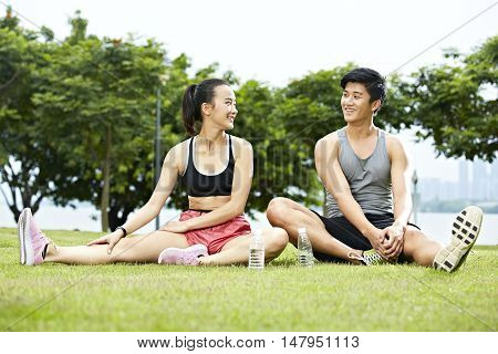 young asian couple or friends talking to each other while stretching legs on grass