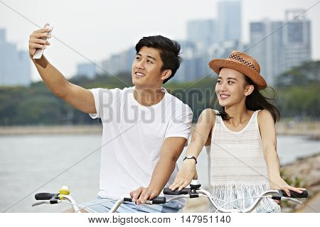 young asian couple taking a selfie while riding bike in urban park