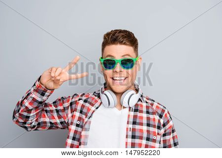 Stylish Guy In Spectacles And Headphones Showing Two Fingers