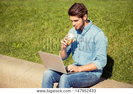 Handsome Guy Drinking Juice And Working On Laptop In The Park