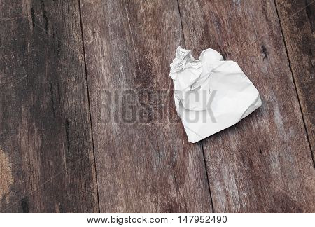 White paper sheet crumpled on a wooden floor background