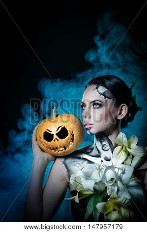 Young attractive girl with creative make-up for Halloween. Close-up portrait with a pumpkin. Mysterious image of lilies and red eyes. Smoke in the background. Jack-o'-lantern