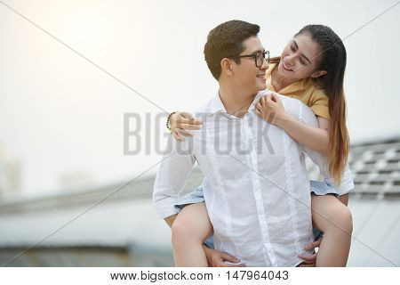 Smiling young man giving piggyback ride to his girlfriend