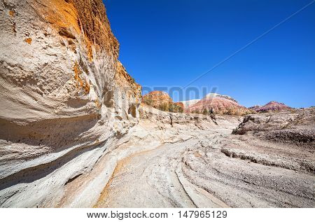 Tourist walking in Altyn Emel National Park with Aktau Mountains at blue sky in Kazakhstan