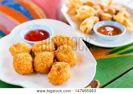 Deep fried chicken nuggets with ketchup on a colored wooden table