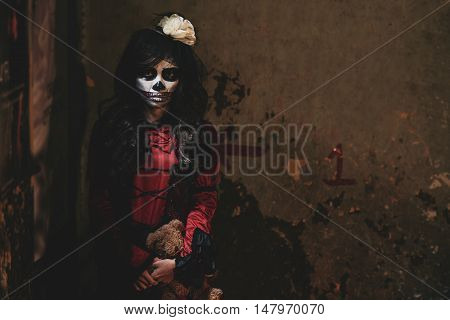 Portrait of bizarre girl with scull face standing in dark corner