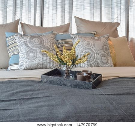 luxury bedroom interior design with striped pillows and decorative tea set on bed