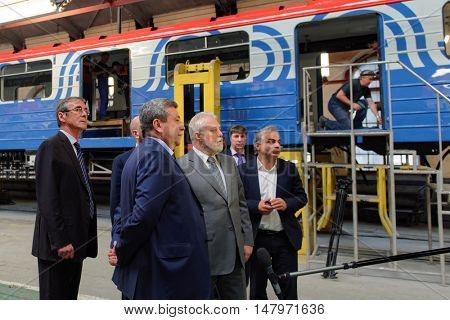 ST. PETERSBURG, RUSSIA - AUGUST 25, 2016: Vice-governor of St. Petersburg Igor Divinsky (gray suit) in the Oktyabrsky electric railway car repair plant. The plant was founded in 1826