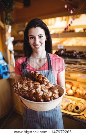 Female baker holding freshly baked loaf of bread in bakery shop