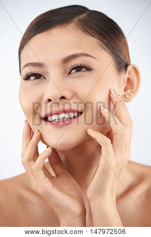 Beautiful woman using hydrating lotion for her skin