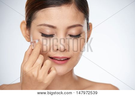 Young Asian woman rubbing face with ice cubes