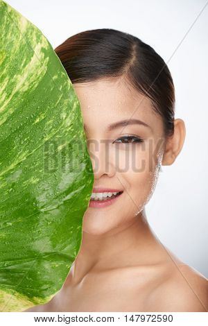 Beautiful Asian woman covering half of her face with large green leaf