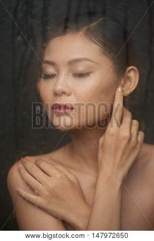 Beautiful Asian young woman enjoying hot shower