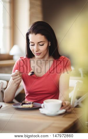 Woman having a slice of cake in bakery shop