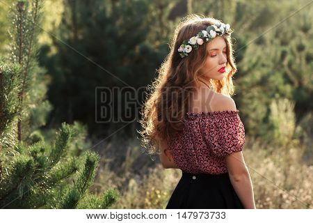 Beautiful girl standing in forest half-turned. Nymph posing near pine-trees. Beauty, nature, relaxation, conservancy, ecology concept