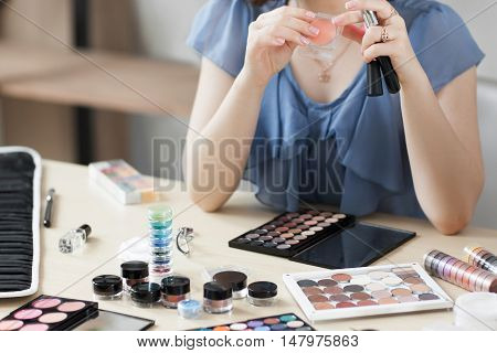 Unrecognizable woman using orange eyeshadows. Stylist workplace with variety of makeup cosmetics