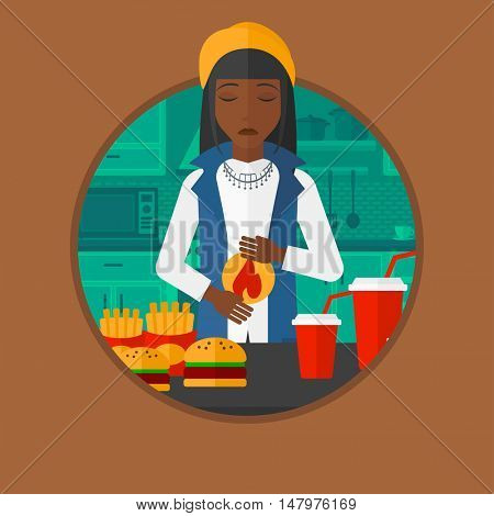 An african woman suffering from heartburn. Woman standing in kitchen in front of table with junk food and suffering from heartburn. Vector flat design illustration in the circle isolated on background