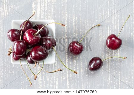 Top view of cherries in white bowl on the grey wooden surface