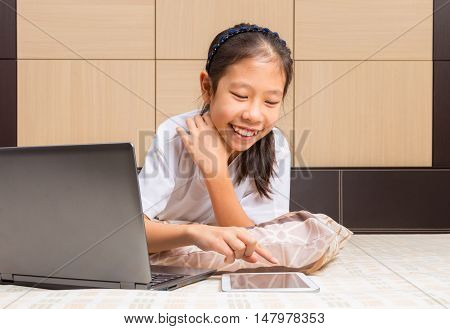 Happy Asian female teenager using technology interacting with moblie computer tablet device in her bed