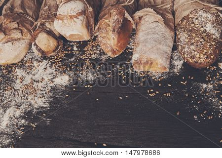 Bread border on dark wood with copy space background. Brown and white whole grain loaves still life composition with wheat flour sprinkled around. Bakery, cooking and grocery store concept. Toned